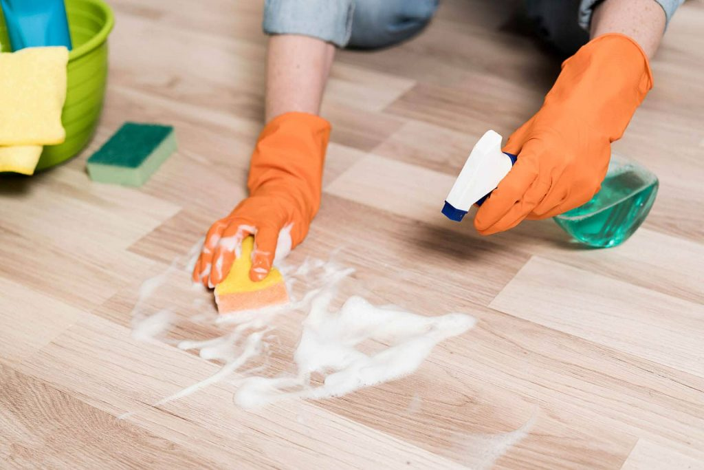 boomtastic woman cleaning floors with sponge and spray